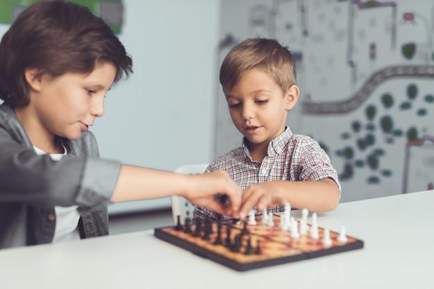 Dois meninos jogam xadrez sentado em uma mesa e estão entediados.