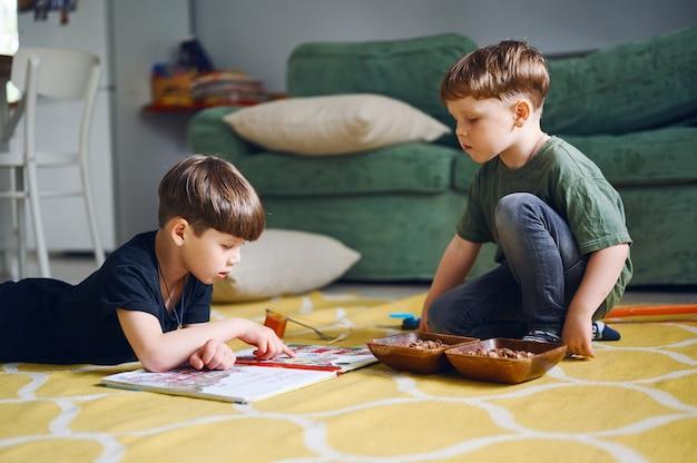 Dois meninos pré-escolares lendo um livro e observando fotos. crianças brancas brincam em casa. crianças comendo lanches no chão