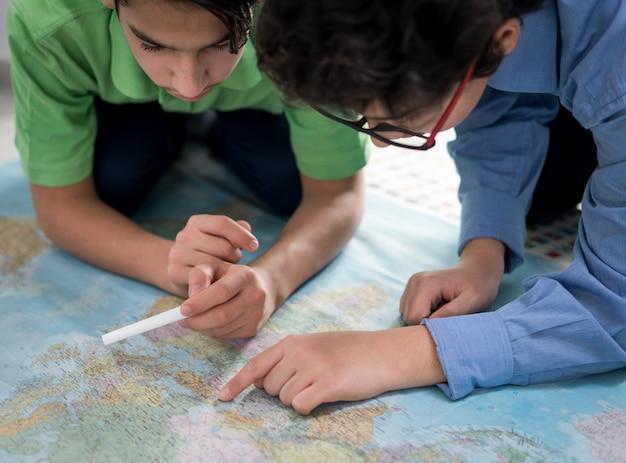 Dois meninos procurando no mapa do mundo