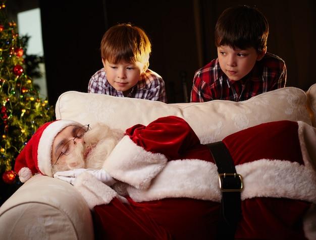 Dois meninos que olham santa dormindo