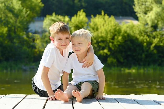 Dois meninos sentados em um abraço nas margens do rio