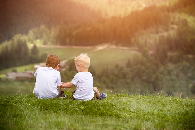 Dois meninos sentam-se na colina