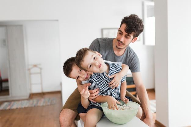 Dois meninos, sentando, com, seu, pai, comer, pipoca