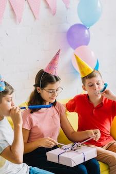 Dois, meninos, soprando, partido, chifre, enquanto, seu, amigo, desembrulhando, presente aniversário