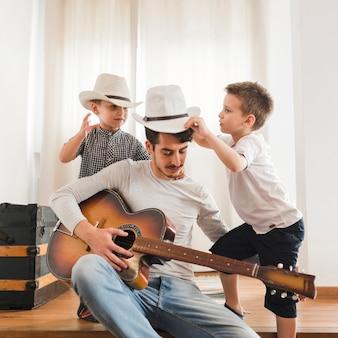 Dois meninos, tocando, com, seu, pai, segurando, violão