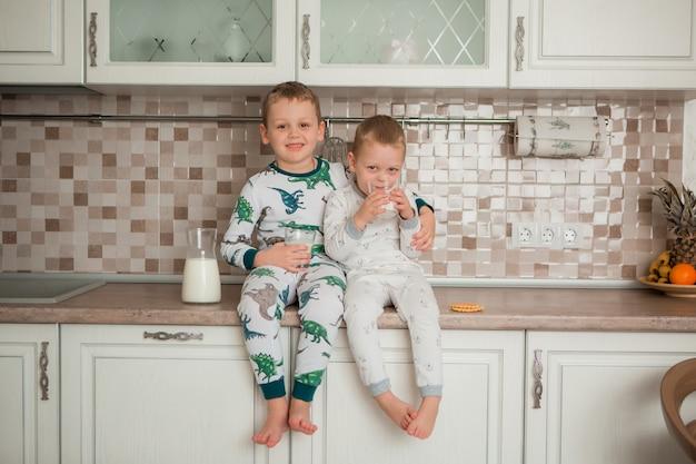 Dois meninos tomam café na cozinha