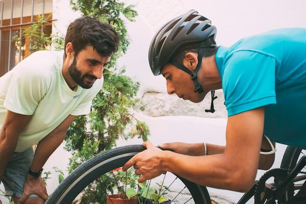 Dois meninos trocando uma roda de bicicleta lá fora. ciclista com um capacete trocando uma roda de bicicleta plana.
