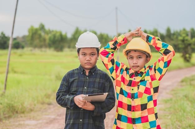 Dois meninos usando capacete engenheiro segurando um tablet em pé ao ar livre