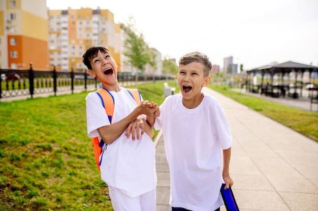 Dois meninos vão para a escola com mochilas brilhantes