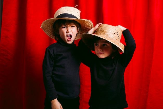 Dois meninos vestindo roupas pretas e uma cabana de palha, contra uma cortina vermelha