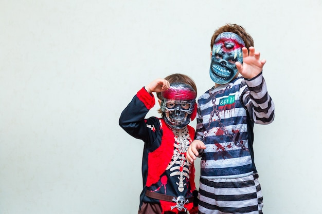 Dois meninos vestindo uma fantasia assustadora com máscaras na luz de fundo, copie o espaço. crianças se preparando para a celebração da festa de halloween em outubro.