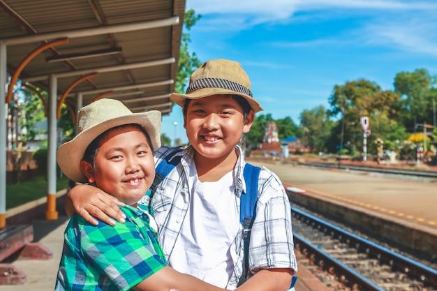 Dois meninos viajam para ficar e aguardar o trem na estação de lopburi, tailândia.