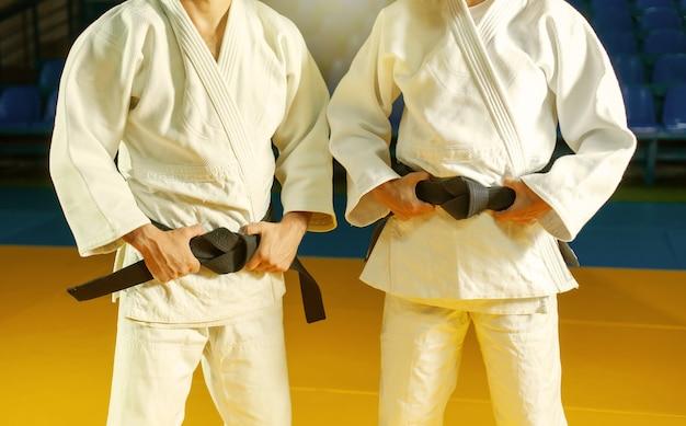 Dois mestres do judô em um kimano branco com faixa preta. cortar foto