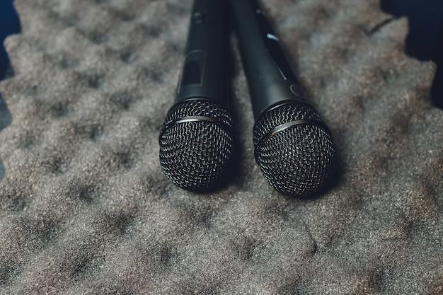 Dois microfones de prata isolados sobre fundo branco