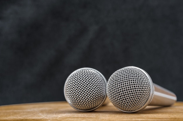 Dois microfones prateados para gravação estão no estúdio em uma mesa de madeira bege