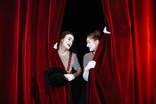 Dois, mime, artista, atrás de, vermelho, cortina, olhando um ao outro