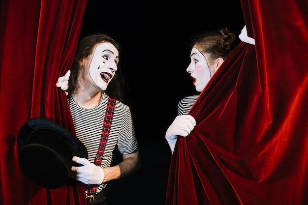 Dois mímica artista realizando por trás da cortina vermelha