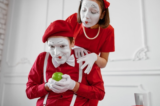 Dois mímicos em trajes vermelhos, cena com maçã