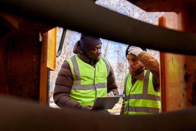 Dois mineiros inspecionando veículo
