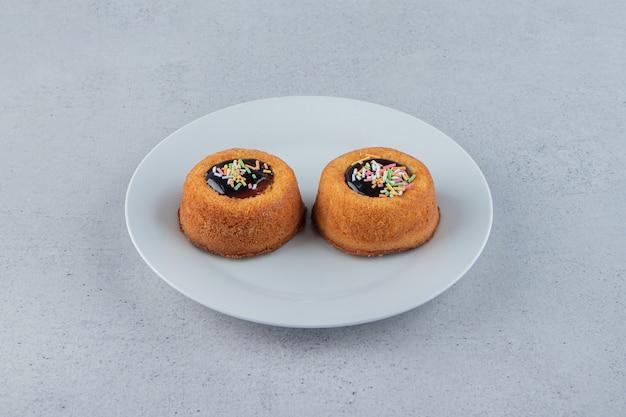 Dois mini bolos com geleia colocados em chapa branca. foto de alta qualidade