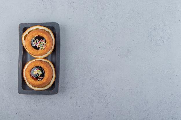 Dois mini bolos com geleia colocados em cima da rodela de laranja. foto de alta qualidade