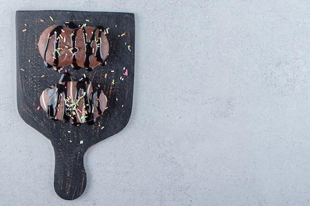 Dois mini bolos de chocolate com granulado na tábua de corte preta. foto de alta qualidade