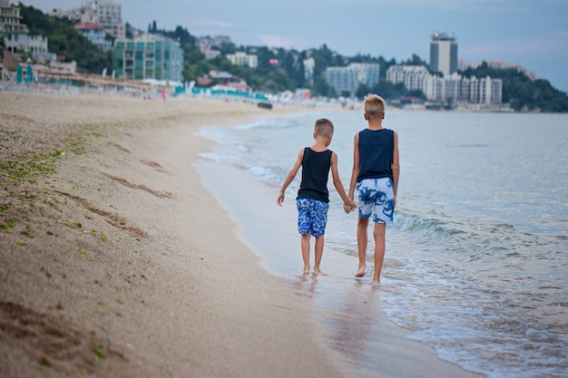 Dois miúdos meninos que andam no verão da praia do mar, melhores amigos felizes que jogam. vista traseira
