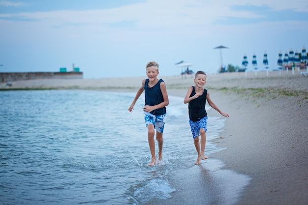 Dois miúdos meninos que andam no verão da praia do mar, melhores amigos felizes que jogam.