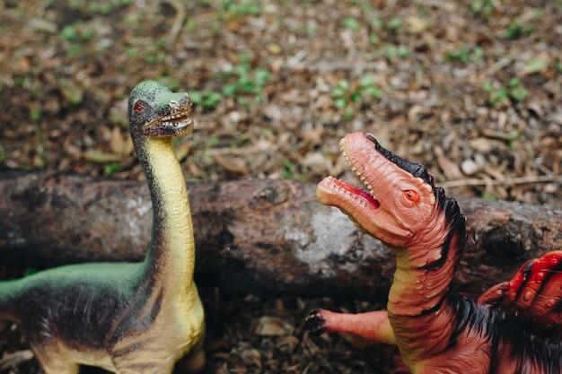 Dois modelos de dinossauros de plástico ao ar livre