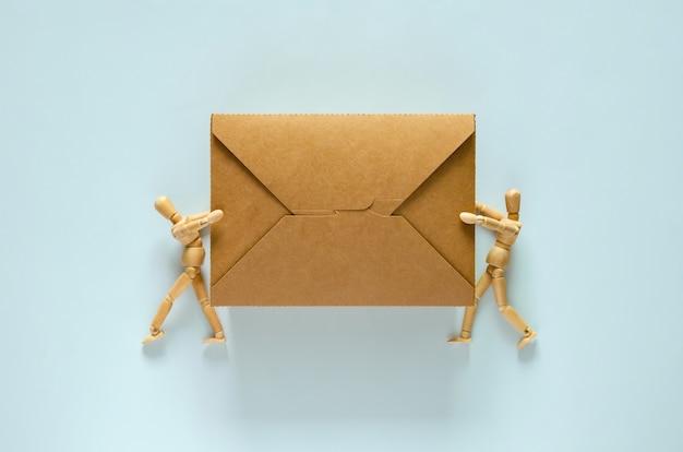 Dois modelos de madeira segurando uma caixa de comida de papel descartável e compostável para o conceito do dia mundial do meio ambiente