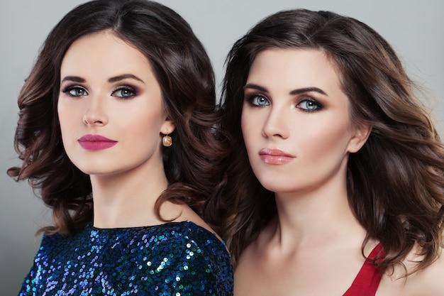 Dois modelos de moda feminina glamorosa. penteado e maquiagem noturno