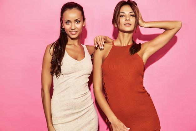 Dois modelos de mulheres bonitas e sorridentes usam vestido de algodão com roupas de tendência de design elegante, estilo casual de verão para data da festa a pé. mulheres quentes morena empresária posando na parede rosa