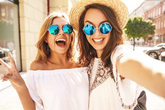 Dois modelos de mulheres jovens loiras e morenas de hippie sorrindo loira no verão hipster branco vestem tirar fotos de selfie para mídias sociais no telefone. cara de surpresa, emoções,