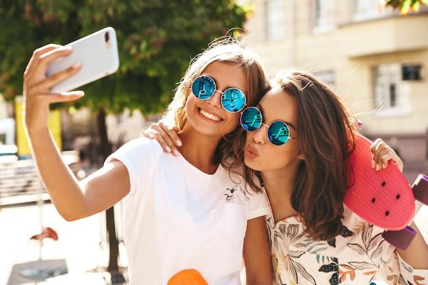 Dois modelos de mulheres jovens loiras e morenas hippie elegante feminina em roupas de verão hipster tirando fotos de selfie para mídias sociais em smartphone