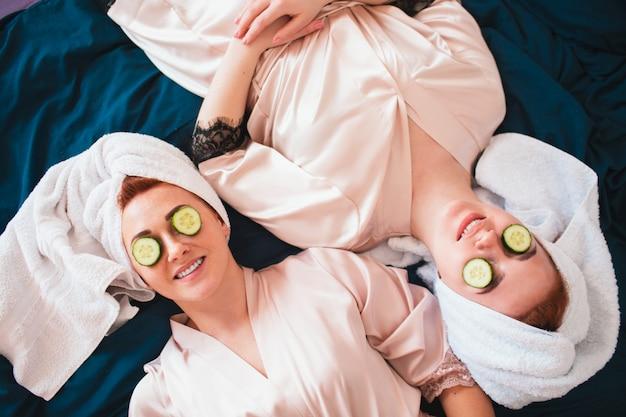 Dois modelos femininos fazem uma máscara de olho usando pepino verde fresco