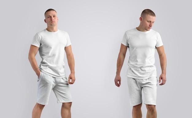 Dois modelos para roupas de apresentação de design. homem caucasiano atlético elegante em uma camiseta em branco e calção cinza de malha em um fundo branco.