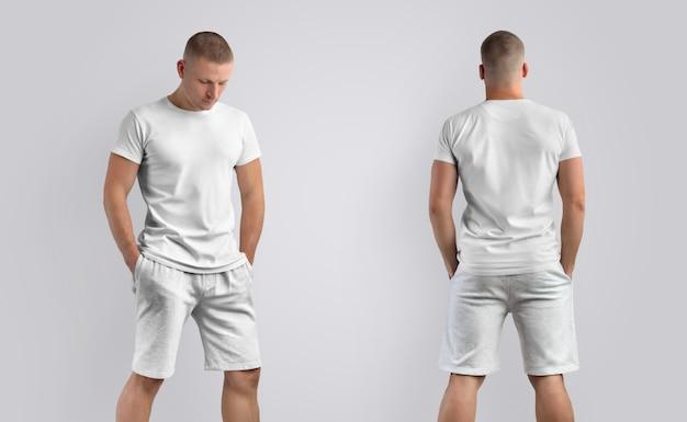 Dois modelos para roupas de apresentação de design. modelo masculino atlético em uma camiseta em branco e shorts cinza de malha isolados em um fundo.