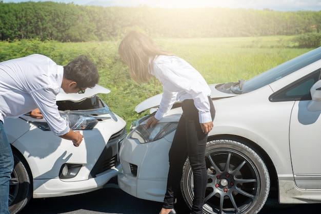 Dois motoristas verificando carros após acidente de trânsito.