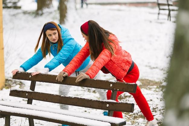Dois, mulher jovem, esticar, perto, a, banco, em, inverno