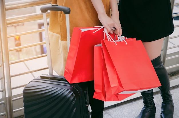 Dois, mulher jovem, segurando, muitos, coloridos, sacolas vermelhas, e, bagagem, andar, junto