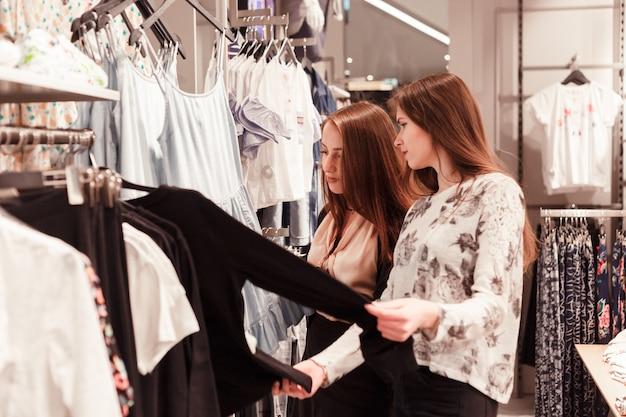 Dois, mulher jovem, shopping, em, loja varejo