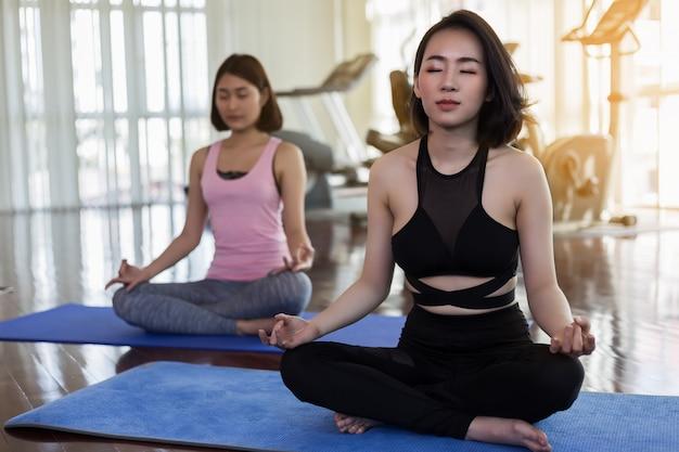 Dois, mulher saudável, fazendo, ioga, em, a, ginásio