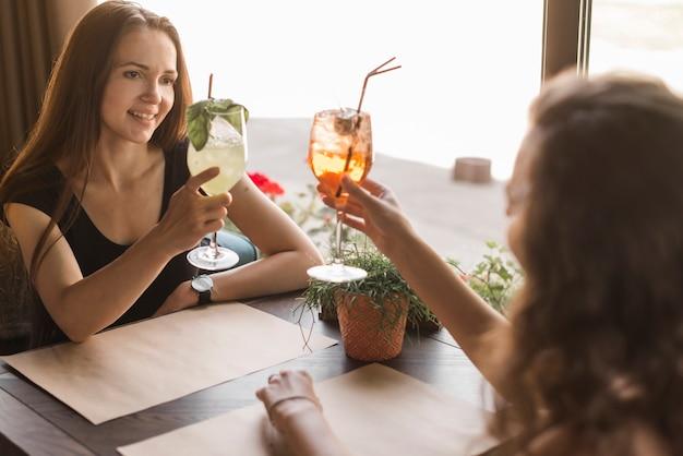 Dois, mulheres, amigos, sentando, em, restaurante, brindar, coquetéis, óculos