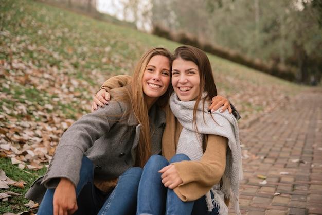Dois, mulheres jovens, abraçando, e, sentando, parque