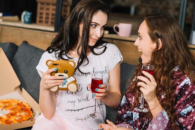 Dois, mulheres jovens, com, bebidas, e, smartphone, olhando um ao outro