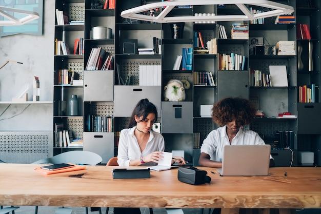 Dois, mulheres jovens, estudar, junto, em, modernos, co, trabalhando, escritório