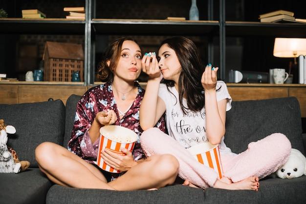 Dois, mulheres jovens, sentando, ligado, sofá, olhando televisão