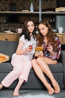Dois, mulheres jovens, sentar sofá, com, bebidas, e, smartphone