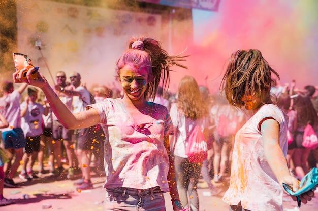 Dois, mulheres jovens, tocando, e, desfrutando, com, holi, cores