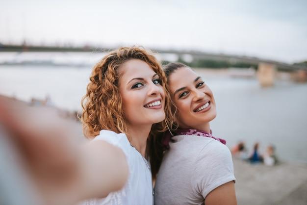 Dois namorada fazendo selfie perto do rio da cidade.